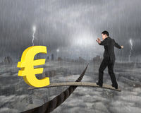 Businessman and euro sign on wood board balancing on wire. Businessman and golden euro sign on wood board, balancing on wire, with stormy mist cityscape Royalty Free Stock Photography