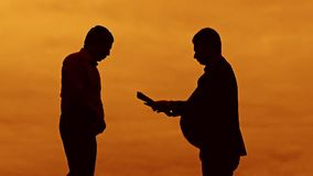 Businessman evil boss discussion sunset silhouette sunlight standing clipboard concept. two businessman men swearing. Outdoors conflict fight looking slow stock footage