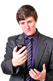 Businessman evil looks at the mobile phone Stock Images