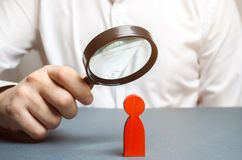 Businessman examines a red man through a magnifying glass. Search for unreliable employee. Weak link. Diagnosis of psychological. And physical diseases stock photo