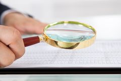 Businessman examining audit with magnifying glass in office Royalty Free Stock Photo