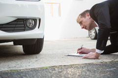 Businessman examining car tire while writing on clipboard Stock Image