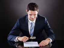 Businessman examining contract paper with magnifying glass Stock Photo