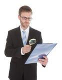Businessman Examining Document On Clipboard Royalty Free Stock Photos
