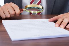 Businessman examining document with magnifying glass Stock Image