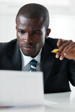 Businessman examining documents. Young adult afro-american businessman examining documents indoors stock photography