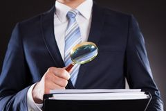 Businessman examining documents with magnifying glass Stock Image