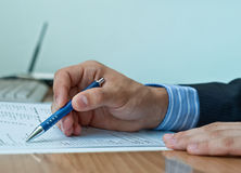 Businessman examining financial document. A businessman points to financial document with a pen and examines the results Royalty Free Stock Images