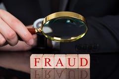 Businessman examining fraud blocks through magnifying glass royalty free stock image