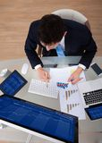 Businessman examining graphs at desk Royalty Free Stock Photos