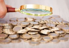 Businessman examining heap of coins through magnifying glass Royalty Free Stock Photography