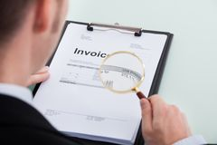 Businessman examining invoice through magnifying glass Royalty Free Stock Photography
