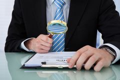 Businessman examining invoice through magnifying glass Royalty Free Stock Photo