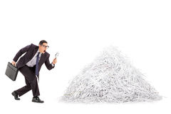 Businessman examining a pile of shredded paper Stock Image