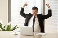 Businessman excited because of achievement in business. Millennial businessman raising hands and happily yelling when looking on laptop at desk. Business leader Stock Image