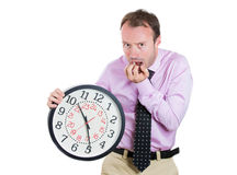 Businessman, executive, leader holding a clock, very determined, pressured by lack of time, running out of time Royalty Free Stock Photo