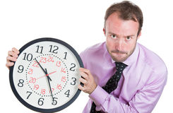Businessman, executive, leader holding a clock, very determined, pressured by lack of time, running out of time, late for the meet Stock Photography