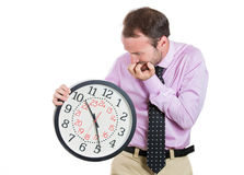 Businessman, executive, leader holding and looking anxiously at a clock, biting his nails, pressured by lack of time Stock Image