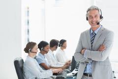 Businessman with executives using computers Stock Photos