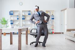 The businessman exercising in office wearing vr glasses Stock Photo
