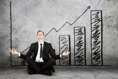 Businessman exercising yoga near growth chart Royalty Free Stock Photo