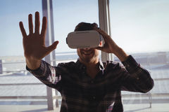 Businessman experiencing virtual reality in creative office Stock Image