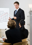 Businessman explaining chart. Businessman explaining a line graph Royalty Free Stock Photography