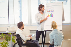 Businessman explaining multi colored graph to colleagues Stock Photos