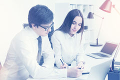 Businessman explaining. Young businessman making notes together with businesswoman who is sitting next to him. Concept of explanation. Toned image stock photo