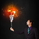 Businessman with an explosion bulb Stock Photo