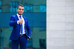 Businessman expressing positivity standing outdoors on office bu. Ilding background, copy space royalty free stock photo