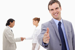 Businessman extending hand with hand shaking colleagues behind h Royalty Free Stock Image