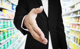 Businessman extending hand. with supermarket aisle background, selective focus Royalty Free Stock Photos