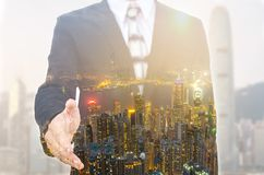 Businessman extending hand to shake with city scape. Stock Photo