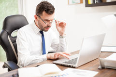 Businessman with eye fatigue working in an office Stock Photography