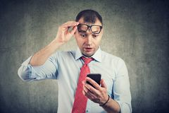Businessman in eyeglasses watching smartphone in shock reading message. Businessman in blue shirt and eyeglasses watching smartphone in shock reading message royalty free stock photo