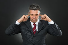 Businessman With Eyes Closed And Fingers In His Ears Stock Photo