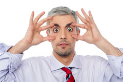 Businessman with eyes wide open. Aged man opened eyes with your fingers Stock Photography