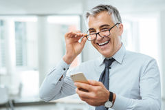 Businessman with eyesight problems. Smiling businessman with eyesight problems, he is adjusting his glasses and reading something on his mobile phone Stock Photo