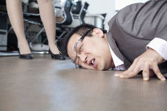 Businessman with face on the floor, coworker standing by him Stock Photography