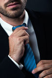 Businessman without face straightens tie yourself. Isolated on b Stock Photography