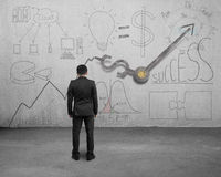 Businessman facing statistics doodles with clock hands. Businessman facing statistics doodles on wall with clock hands Stock Photo