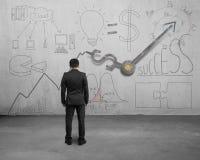 Businessman facing statistics doodles with clock hands Stock Photo