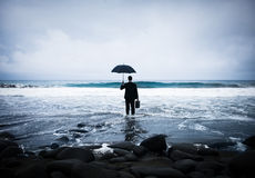 Businessman Facing Storm on the Beach Royalty Free Stock Image