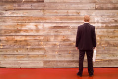 Businessman facing a wall. Businessman holding briefcase facing wooden wall Stock Photos