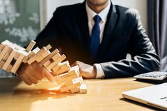 Businessman fail danger tower challenge game. Building consturction protect plan and project for control risk shape with paperwork Stock Photo