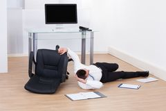 Businessman fallen from office chair Stock Images