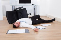 Businessman fallen from office chair Royalty Free Stock Photography