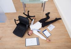 Businessman fallen from office chair Royalty Free Stock Images