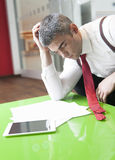 Businessman falling asleep whilst reading documents Royalty Free Stock Image